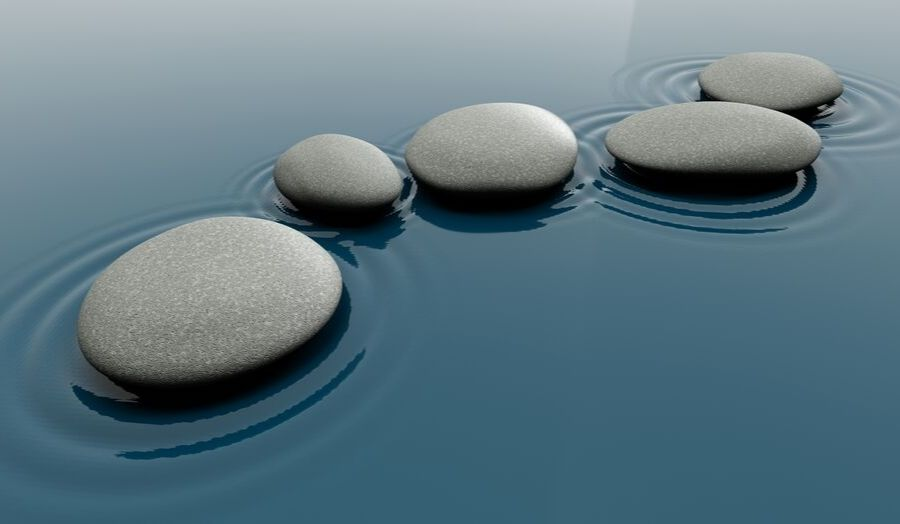 Five pebbles in blue water with ripples in the water coming from the pebbles