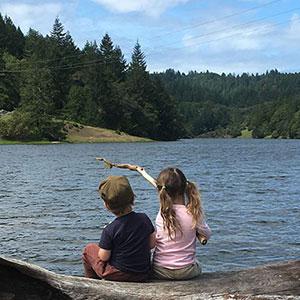 children sitting by a lake