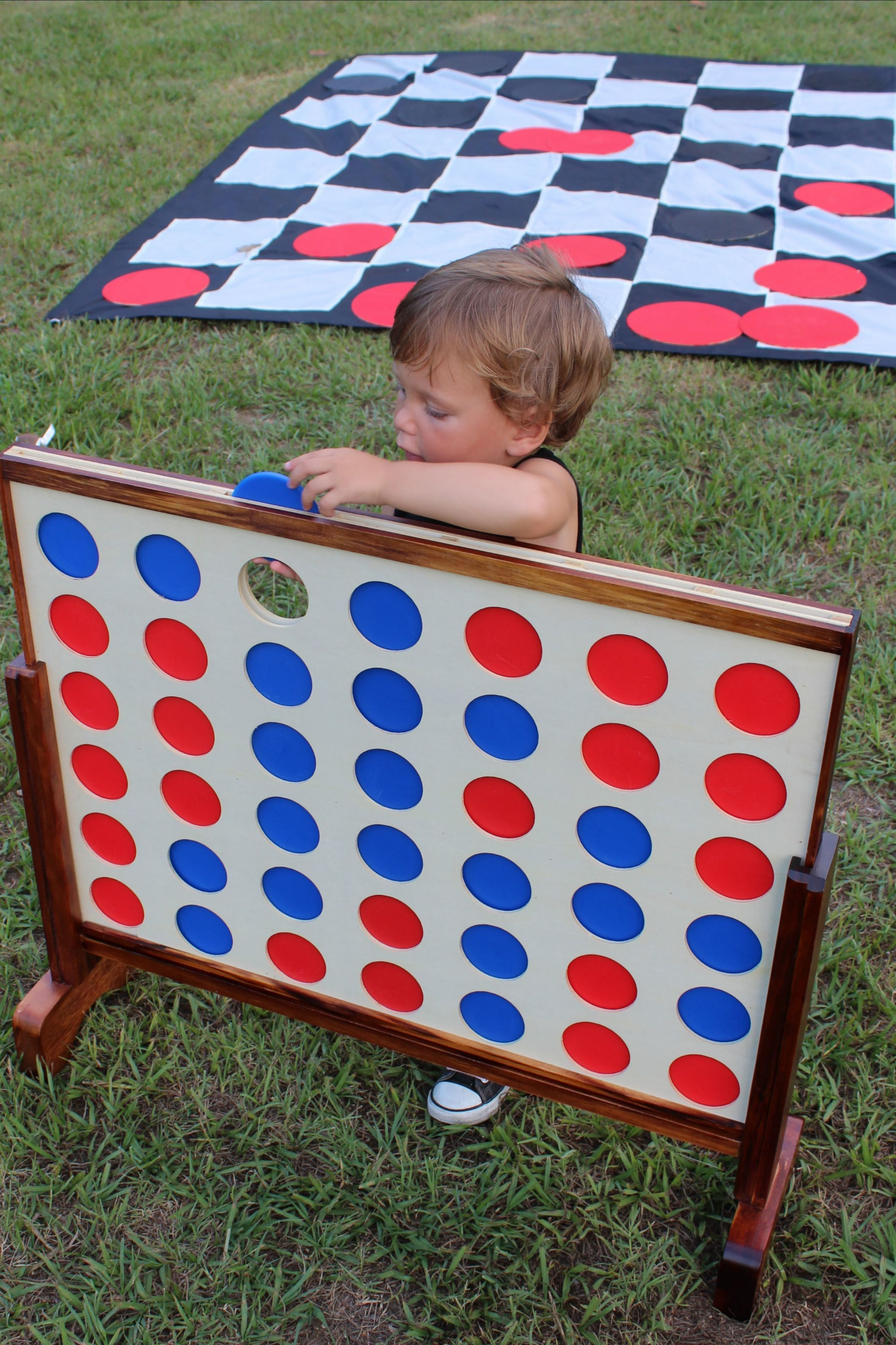 Toddler playing life-size Connect Four