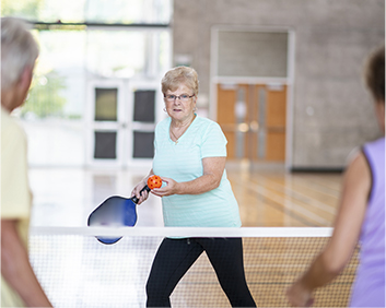 Woman preparing to serve the ball in pickleball match