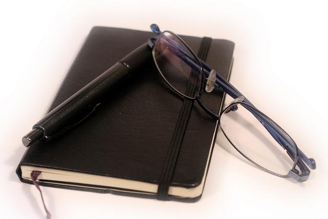 adressenboek, pen en bril
