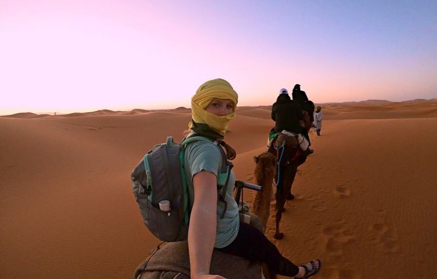 A student takes a selfie atop a camel in the middle of the Sahara Desert.