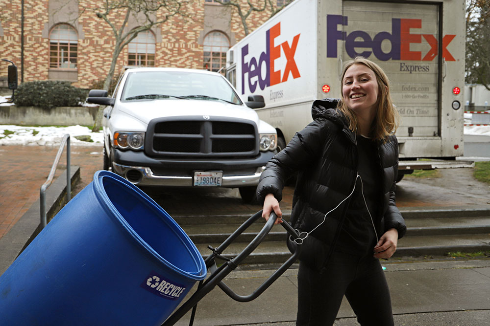 A student employee of the AS Recycle Center smiles as she hauls a large blue barrel on a dolly.