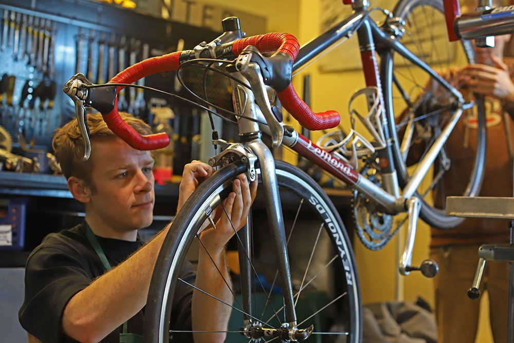 A student repairs his bicycle at a repair station at the Outdoor Center bike shop.