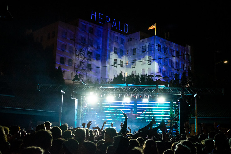 A nighttime scene of a concert behind the Herald Building. Audience members' heads and hands can be seen in the foreground -- along with the legs and feet of an audience member who is apparently crowd surfing.