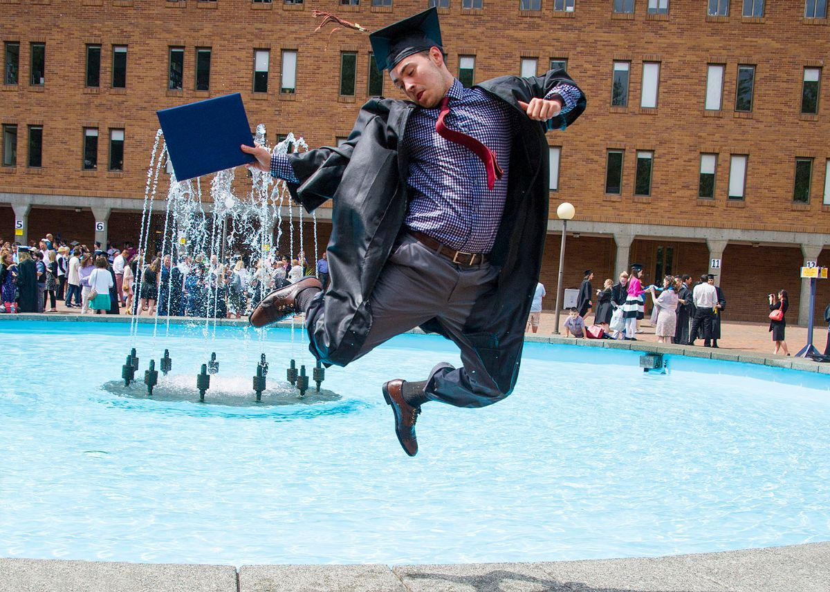 A student in graduation regalia and holding a diploma leaps with joy next to Fisher Fountain.