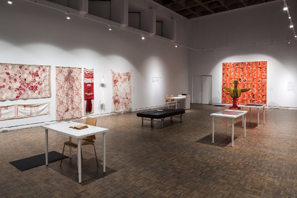 This image depicts a part of the Mount Saint Vincent University Art Gallery Bodies in Translation show on Aging and Creativity. There are five tables, four white and one shorter black table, dispersed throughout the room, and seven red and white tapestries in various prints on the white walls. There is a brown statue near the back right hand side of the room.