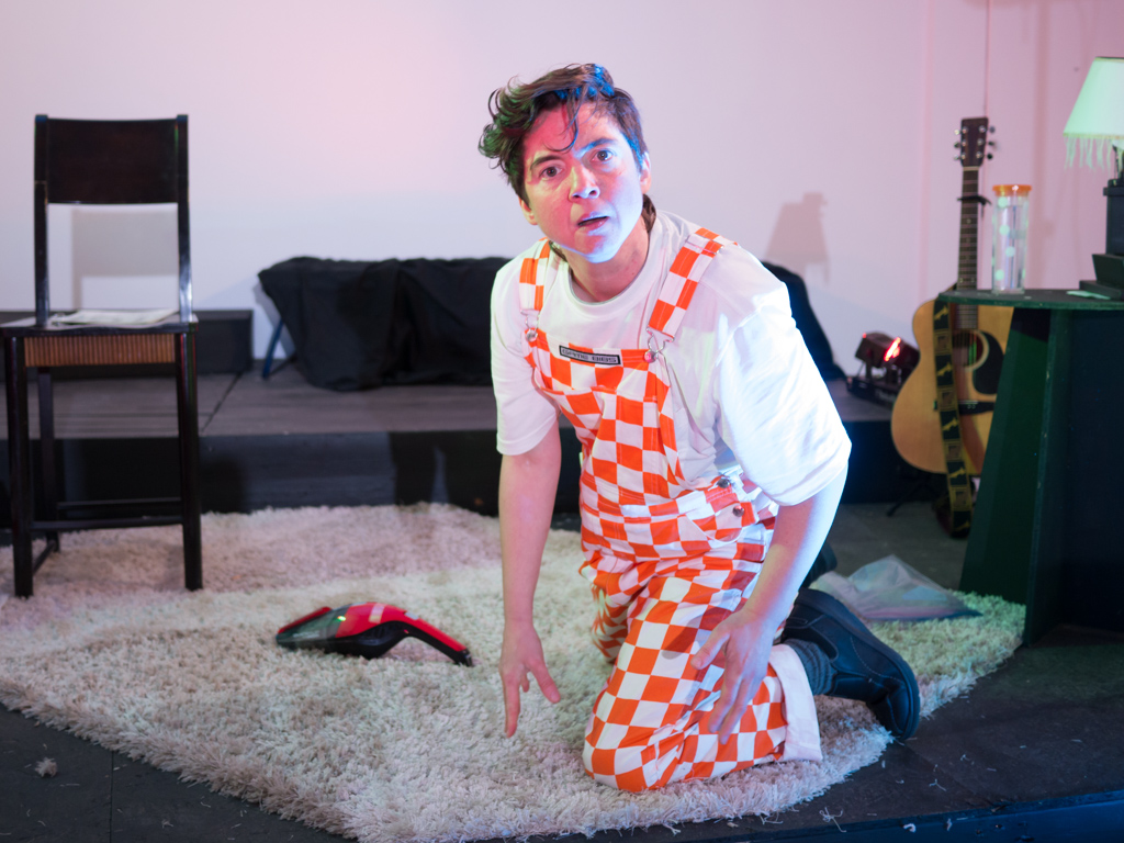 A photo of Em Glasspool performing in Wreck Wee Em. They have short dark hair and a bewildered expression. Em is wearing orange and white checked overalls and kneeling on a rug, which is part of the set that looks like a living room.