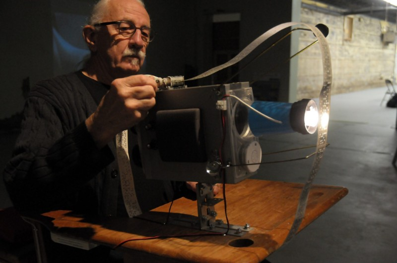 David Bobier is to the left side of the photo, wearing glasses and a black sweater with his hair in a ponytail, adjusting a vibro-projector machine on a wooden table.