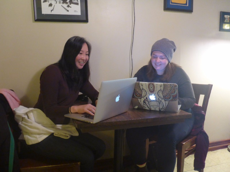 Photo of Dr. Nadine Changfoot and Annette Pedlar. The two are sitting facing each other at a table, each with a Macbook laptop open and angled slightly outward toward the camera.