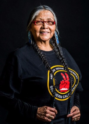 "This image is a colour photograph of an Anishinaabe Elder, standing, facing forward, in front of a black background. She is wearing a black tshirt that depicts a red hand giving the peace sign and reads ""American Indian Movement Southern California."" She is smiling and her hands are in front of her waist holding the two long braids in her hair."