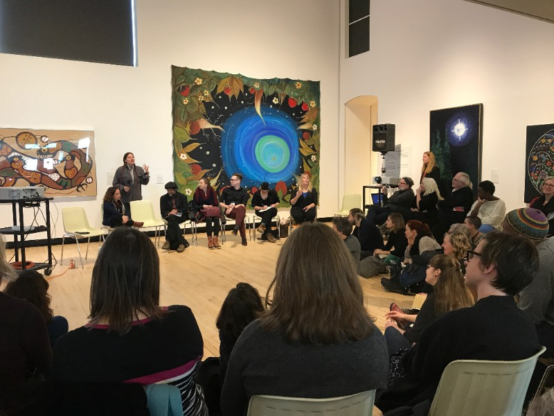 "This image is of a group of people in a semi circle with Dolleen Manning standing up and speaking. Behind Dolleen is a large painting entitled ""What Comes From Above"" (1997) by artist Shelley Nero. The painting depicts large blue circles within circles with multicoloured plant and sky details around it."