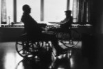 Two people in wheelchairs are silhouetted against a window