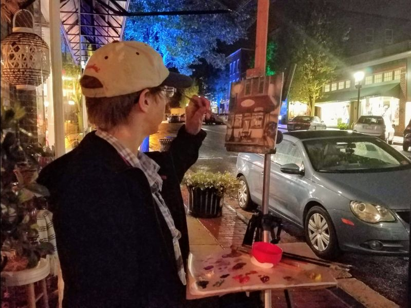 photo of a person painting a streetscape outdoors at night