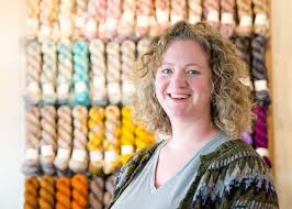 Photo of a woman stood in front of skeins of yarn