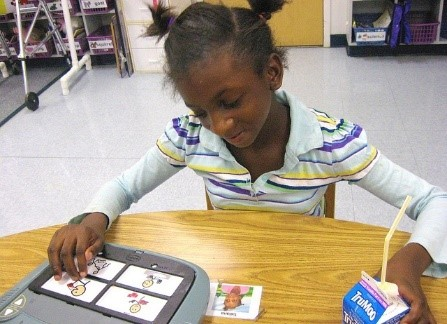 A child with autism using a board with communication cards and pictures