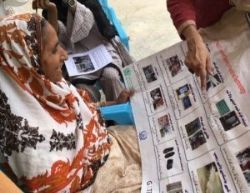 rATA survey pilot in a household in Pakistan: a woman is looking at the survey and selecting assistive products she might need