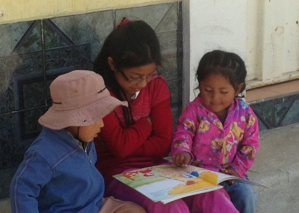 Evelyn reads to Yosvin and Andrea