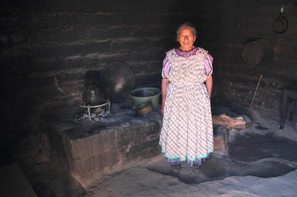 "Doña Margarita standing beside her old ""stove,"" an open fire. Photo by Juan Burlew"