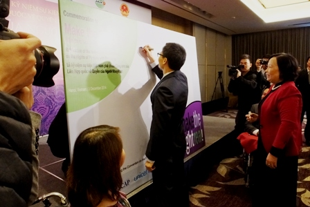 "Deputy Prime Minister H.E. Mr. Vu Duc Dam signing the ""Make the Right Real"" pledge board"