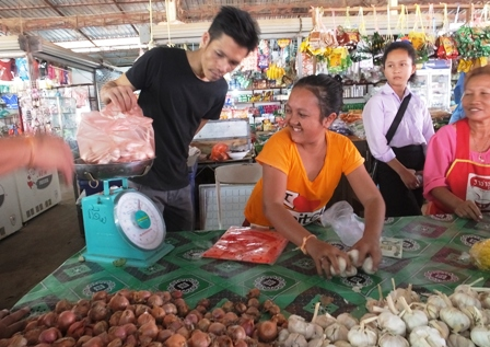 Person with disability enjoying a free market stall in Nong Sa Market, Naxaithong, Lao PDR
