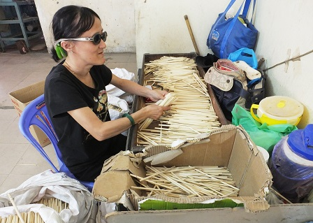 Person with disability sorting out chopsticks at the Bamboo Dana Ltd. factory