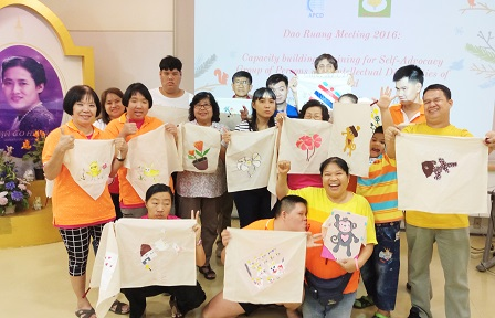 Group photo with Dao Ruang members, their parents and supporters featuring their artwork