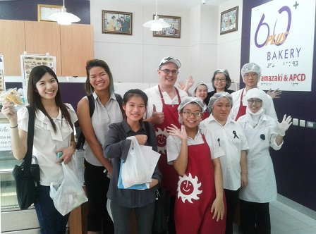 Group photo of visitors, 60 Plus+ Bakery & Cafe staff/trainees with disabilities and APCD Staff