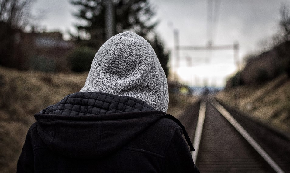 Person in hoodie looking away and down railway tracks