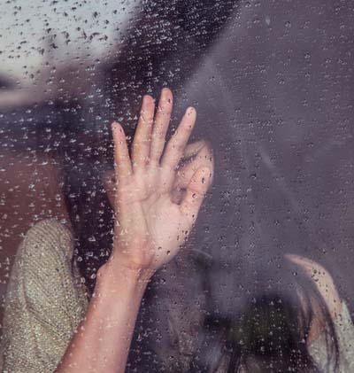 Young girl looking out of rainy window with hand in front of face