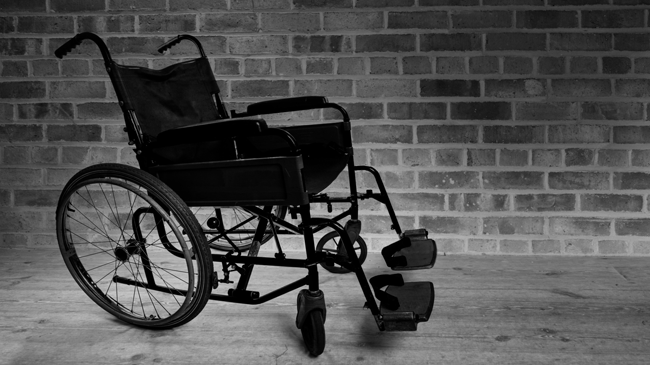 Empty wheelchair in front of brick wall