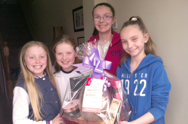One woman and three girls holding an easter egg hamper