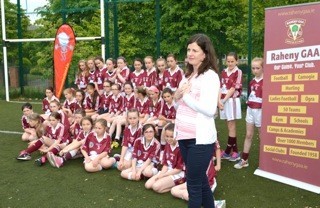 Auveen Bell standing with a team of young femae GAA players in their Blossom sponsored kit.