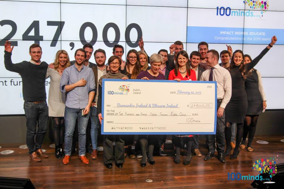 A large group of cheering people standing behind an oversized cheque on a stage.