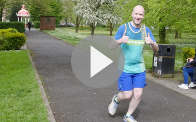 Image of volunteer John running, with play button overlaid