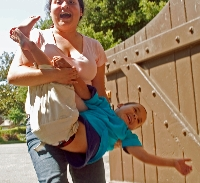 Mother carries delighted boy