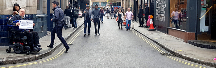 Picture showing chris on one side, unable to cross the street because there are no drop kerbs.
