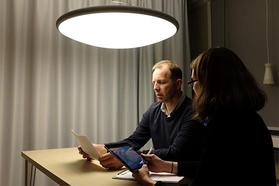 Une personne déficiente visuelle lis un document sous une lampe afin d'en tester la luminosité