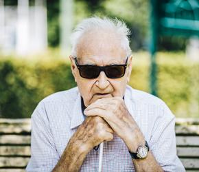 Een blinde persoon kijkt naar de camera terwijl ze een witte stok vasthoudt.