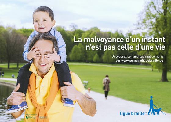 Un père porte son enfant sur ses épaules lors d'une promenade. L'enfant lui cache les yeux avec ses mains en riant.