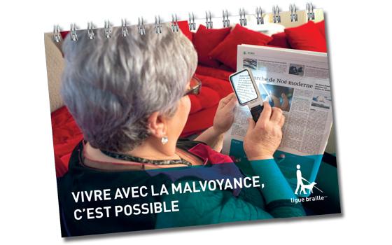 Première de couverture du guide 'Vivre avec la malvoyance, c'est possible'. Une personne lis son journal à l'aide d'une loupe.