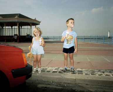 Two children standing on a pavement by the seaside eating melting ice-creams