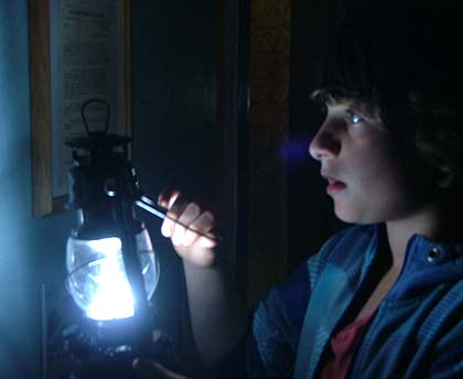 A boy using a lantern to look at a museum display