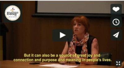 """A screenshot showing Rosalie Power, one of the seminar speakers sitting at a desk. Subtitiled wordsappear across the bottom of the image  saying """"But it can also be a source of joy and connection and purpose and meaning in people's lives."""""""