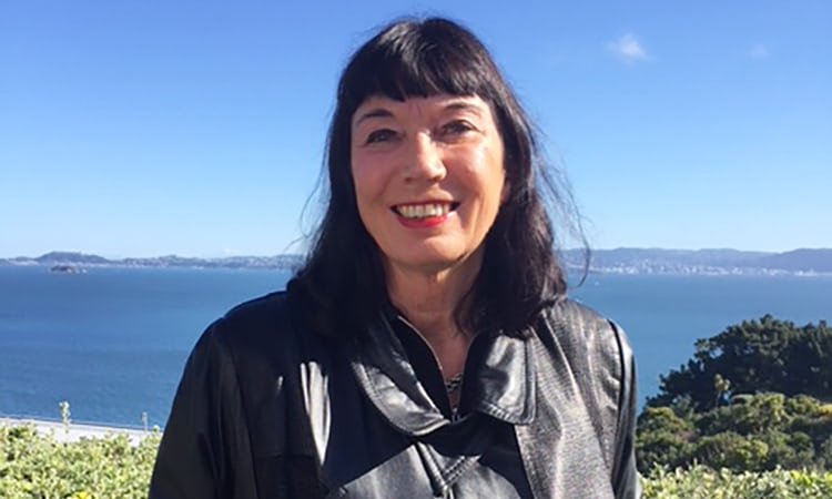 A head and shoulders picture of a smiling Dame Catherine Healy, with a large bay of water in the background  against