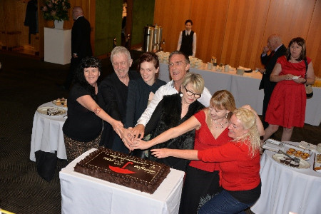 Seven sex worker representatives holding a knife for a ceremonial cutting of a large chocolate cake iced with a large red unbrella and the words Celebrating 20 years of decriminalisation. There are several people standing in the background beside tables set with afternoon tea.