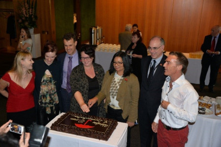 Four members of NSW Parliament are standing beside a celebratory cake, flanked by three sex workers and with several other people watching in the background