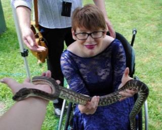 Kelly Vincent is sitting looking upwards towards the camera and holding a snake, which is climbing onto the arm of another person. There is someone standing in the background ready to grab the snake in case it tries bite her.
