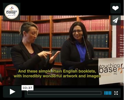 "Screen shot of an Auslan interpreter translating Dr Mehreen Faruqi giving a speech at a podium. There is a Touching Base logo and a subtitle that says ""And these simple Plain English booklets, with incredibly wonderful artwork and images"""