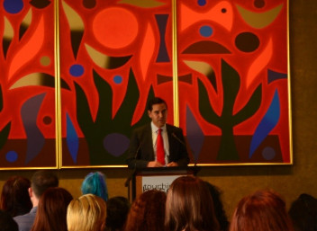 MP Alex Greenwich standing at a podium in front of people sitting in the audience with a colourful tapestry in the background
